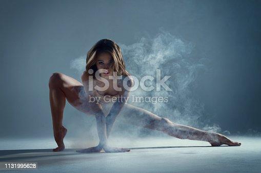 istock Muscle woman dancer dancing with smoke on isolated background 1131995628