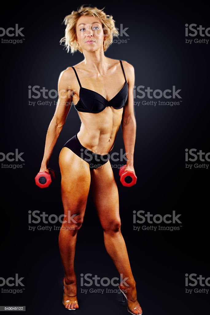 muscle woman does sports exercises stock photo