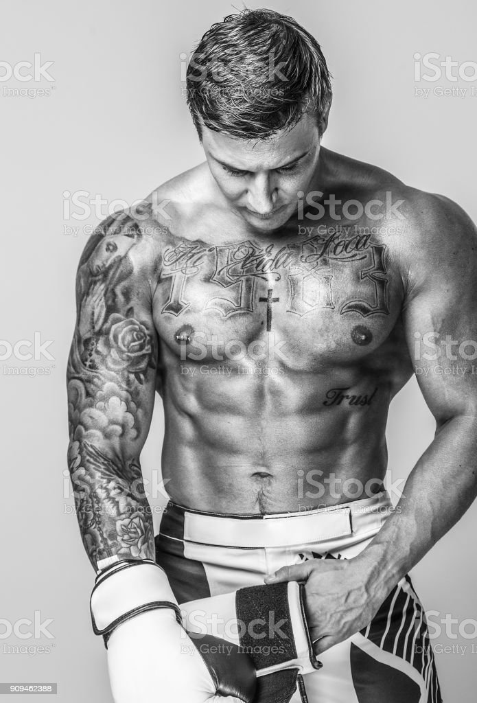 A muscled and tattooed man is putting on boxing gloves stock photo