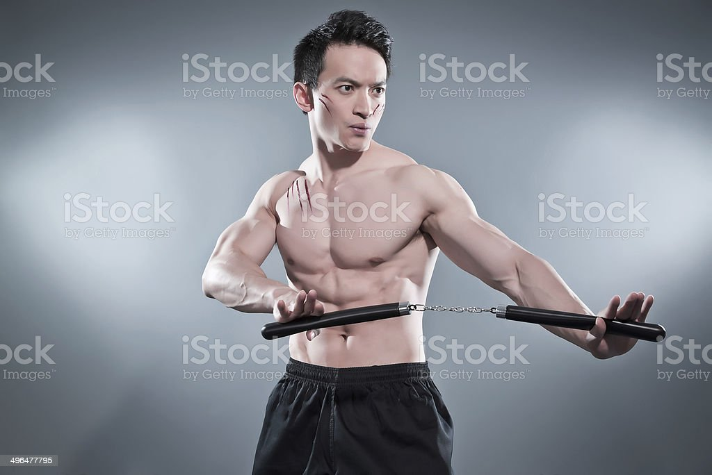 Muscled asian kung fu man in action pose with nunchucks. stock photo