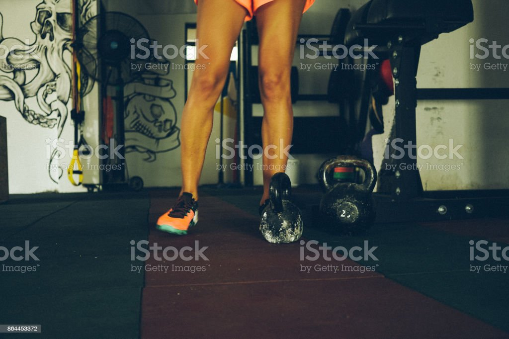 Muscled legs next to kettlebell stock photo