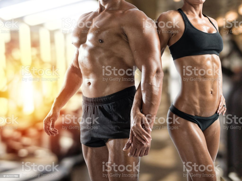 Muscled man and woman at the gym stock photo