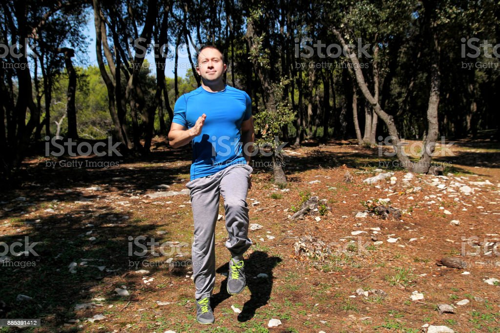Muscled man doing workout run in place exercise in forest. Handsome sportsman wearing sportswear is running in place exercise in beautiful landscape nature outdoors. gym guy, healthy lifestyle. stock photo