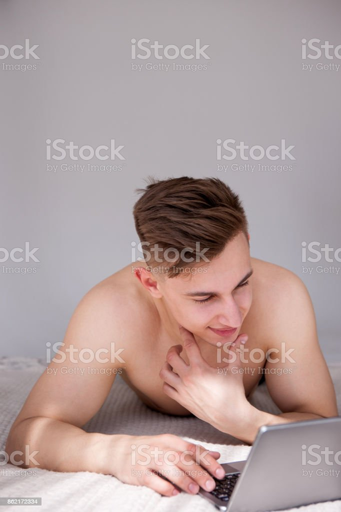Muscled man online chatting with girl on bed stock photo