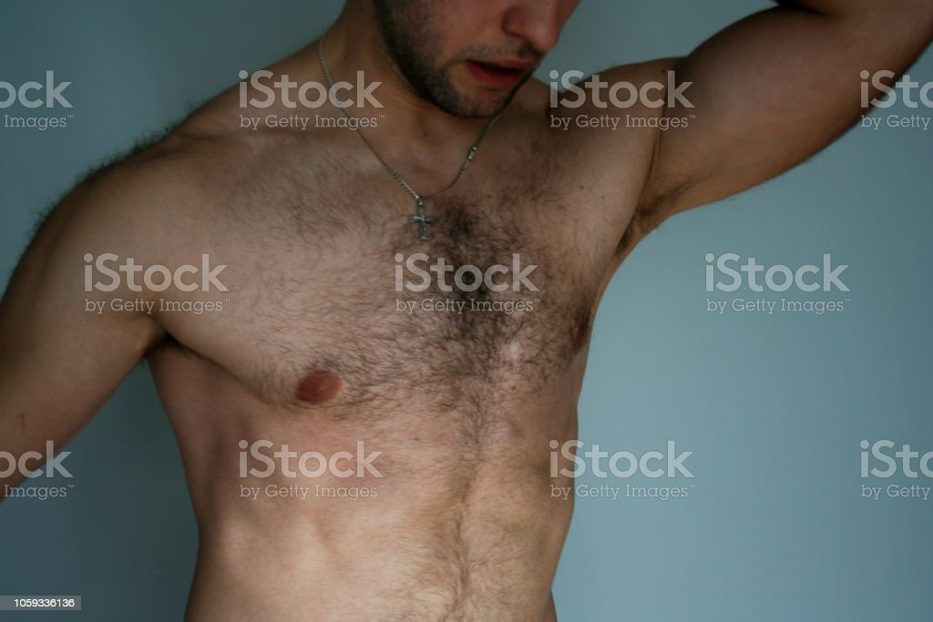 Muscled man presents his muscles. The athletic guy shows his chest...
