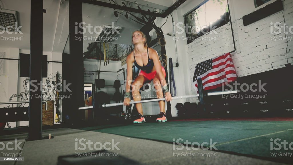 Muscled woman working Romanian deadlifts at the gym stock photo