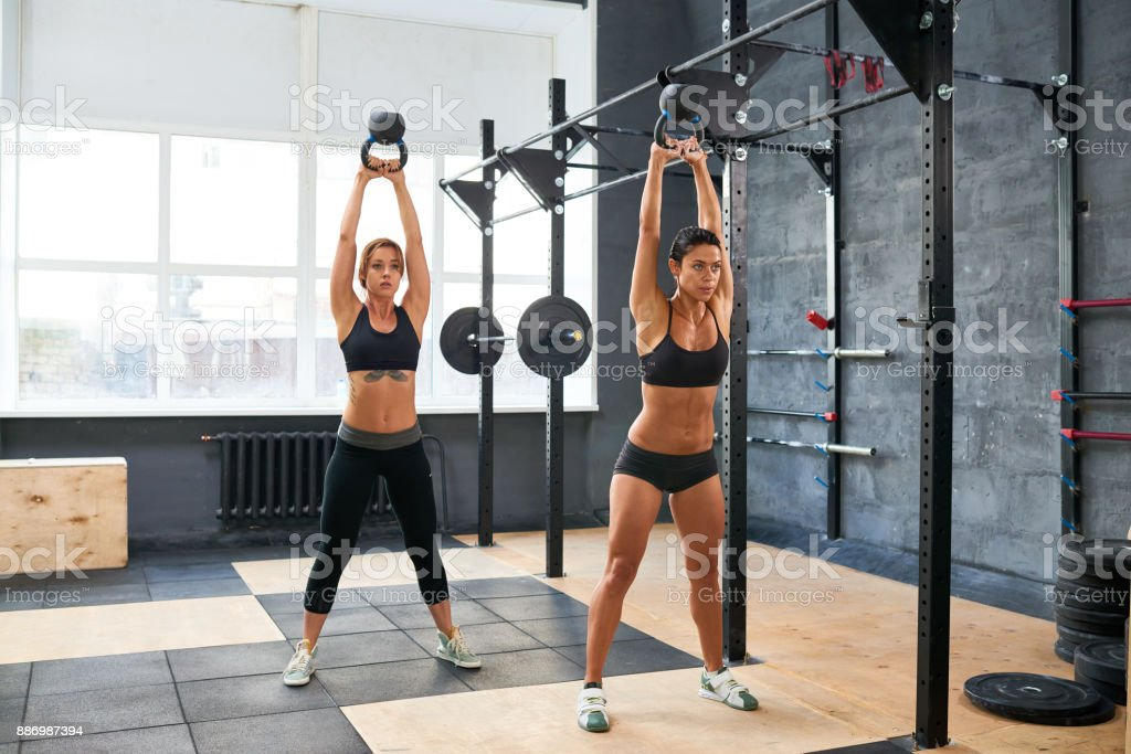 Muscled women working hard in gym stock photo