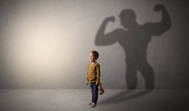 Muscleman shadow behind waggish little boy stock photo