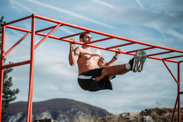 Muscular adult man training in forest stock photo