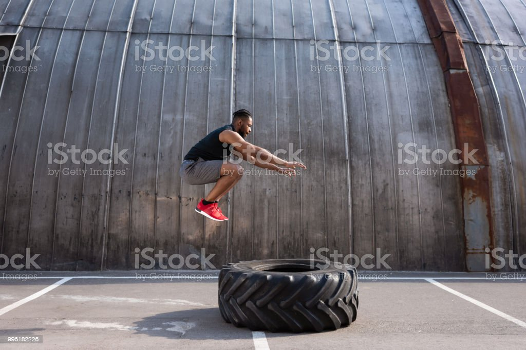 muscular african american sportsman jumping while training with tyre on street stock photo