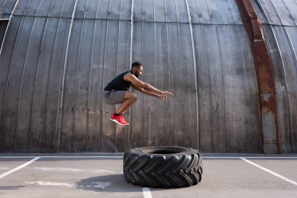 musculaire sportif afro-américain sauter tout en s'entraînant avec pneu sur rue - dressage photos et images de collection