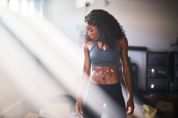 muscular african american woman sweating from work out in home gym muscular african american woman sweating from work out in home gym with light rays abdominal muscle stock pictures, royalty-free photos & images