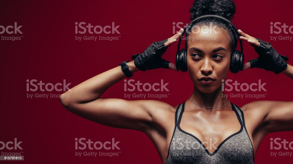 Muscular african female exercising with headphones on stock photo