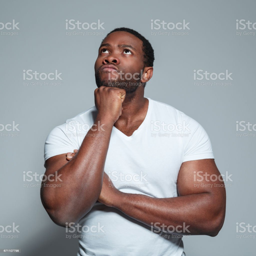 Muscular african man looking up and thinking stock photo
