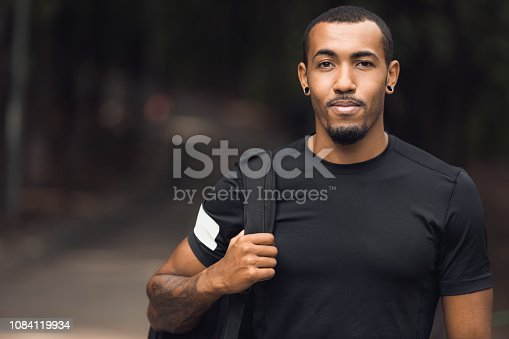 Muscular african-american man wearing black t-shirt and backpack posing outside after workout