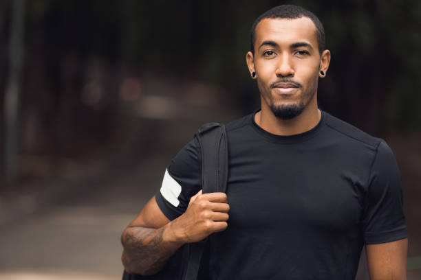 Muscular african-american man posing outside after workout Muscular african-american man wearing black t-shirt and backpack posing outside after workout black shirt stock pictures, royalty-free photos & images