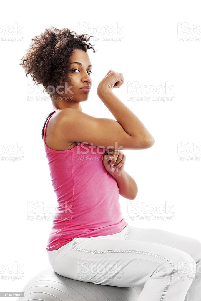 Muscular African-American woman sitting on fitness ball. royalty-free stock photo