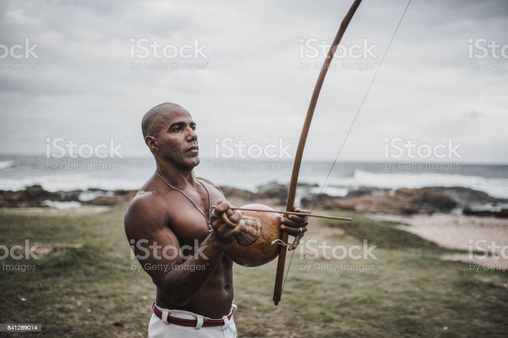 afro-brasileiro muscular homem tocando berimbau ao ar livre - foto de acervo