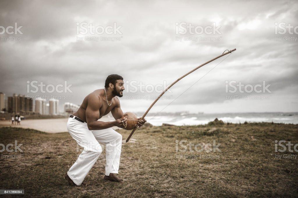homem musculoso afro-brasileiro com berimbau na praia - foto de acervo