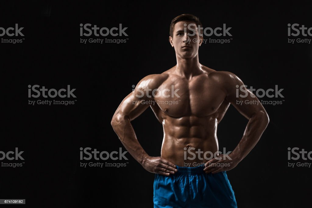 Muscular and fit young bodybuilder fitness male model posing over black background royalty-free stock photo