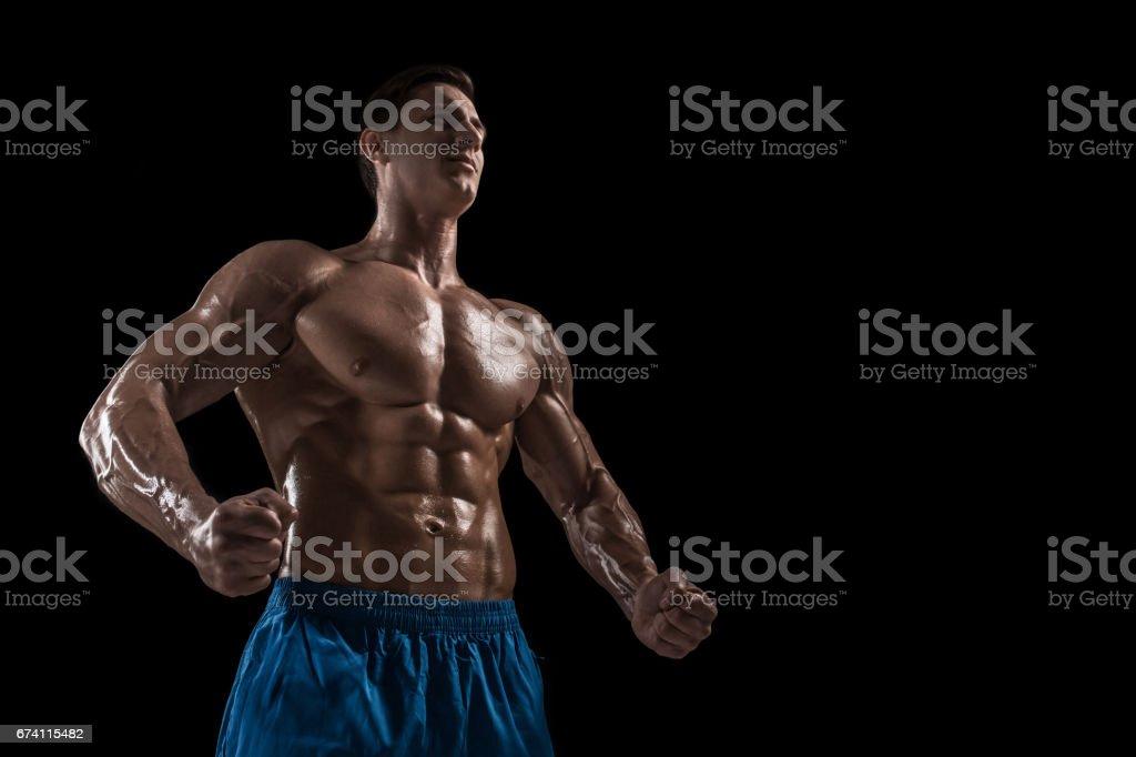 肌肉和身體健康的年輕健美健身男模特在黑色的背景 免版稅 stock photo