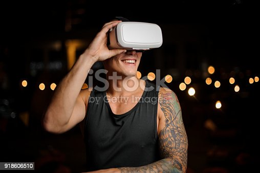 687096686 istock photo Muscular and tattooed smiling handsome man in night vision glasses 918606510