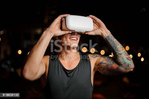 687096686 istock photo Muscular and tattooed smiling handsome man looks in night vision glasses 918609100