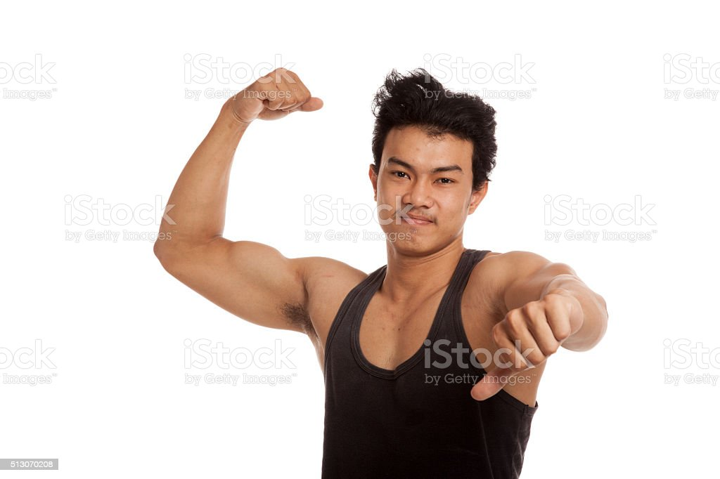 Muscular Asian man flexing biceps and thumbs down stock photo