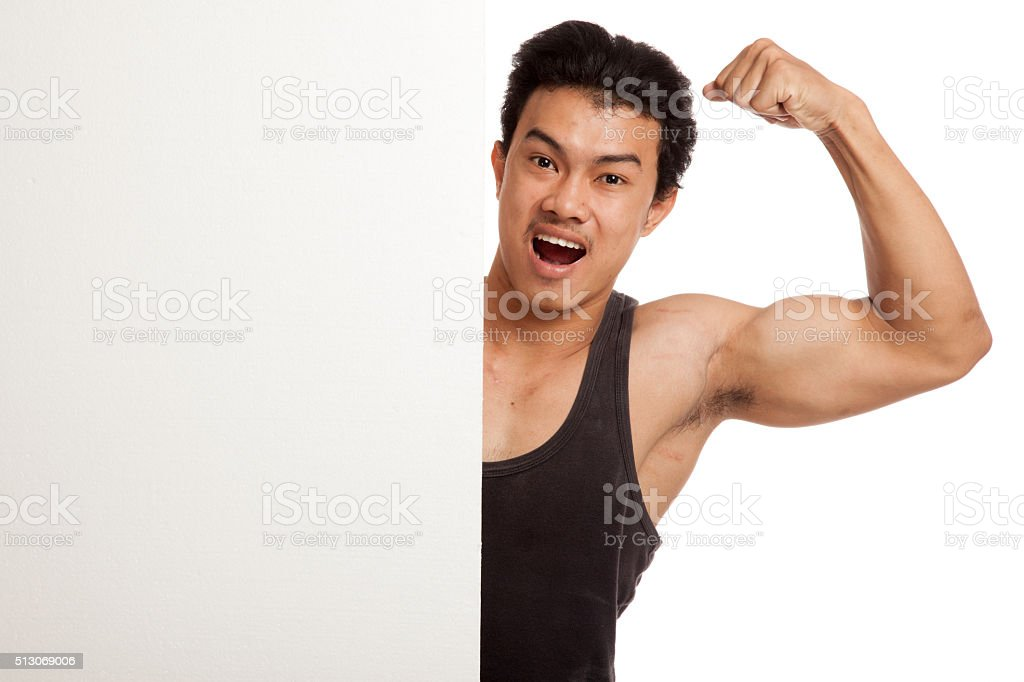 Muscular Asian man flexing biceps behind  blank sign stock photo