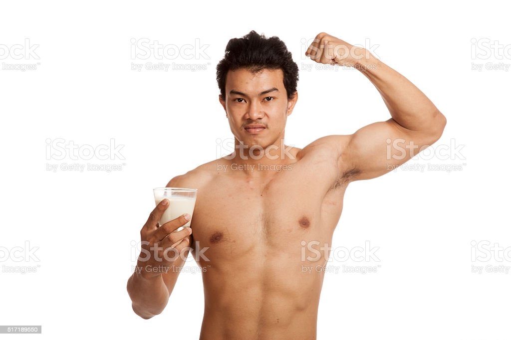 Muscular Asian man flexing biceps with soy milk stock photo