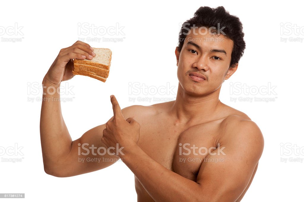 Muscular Asian man load carbohydrate point to bread stock photo