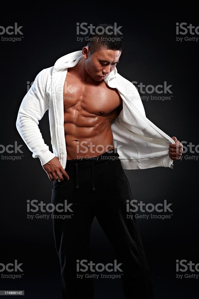 Muscular asian man posing in hooded shirt stock photo