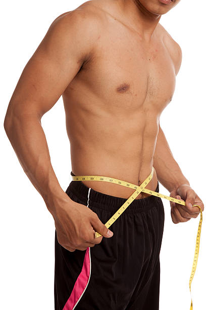 Muscular Asian Man With Measuring Tape Stock Photo