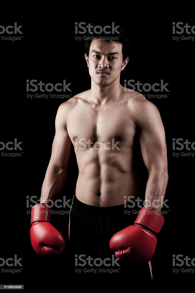 Muscular Asian man with red boxing glove stock photo