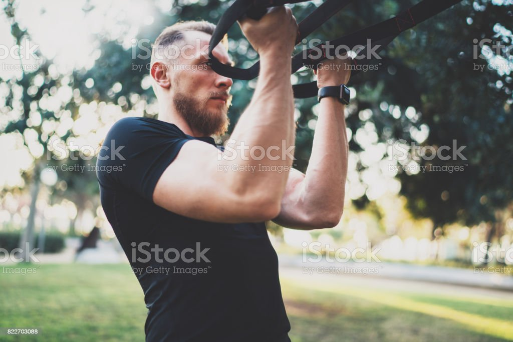 Muscular athlete exercising in park. stock photo