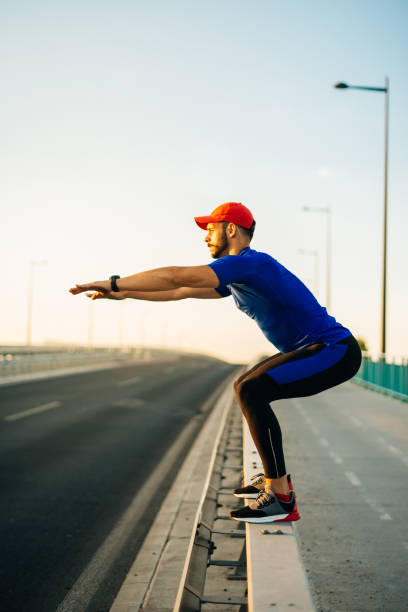 muscular athlete exercising outdoors, near the road in urban district in summer - man city exercise abs foto e immagini stock