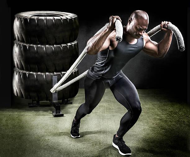 muscular athlete pulling sled of tires. - sachenmacher stock-fotos und bilder
