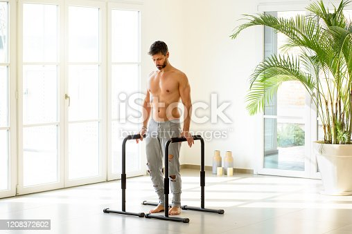 Fit muscular athlete ready to perform calisthenics exercises on parallel bars as the man stands psyching himself up for his workout in a high key gym with copy space