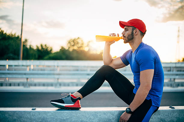 Muscular athlete resting and drinking energy drink stock photo