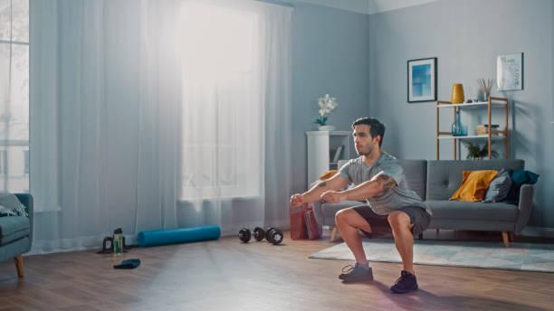 o homem atlético muscular do ajuste no t-shirt e nos shorts está fazendo exercícios da agachamento em casa em sua sala de visitas espaçosa e brilhante com interior minimalistic. - edifício residencial - fotografias e filmes do acervo