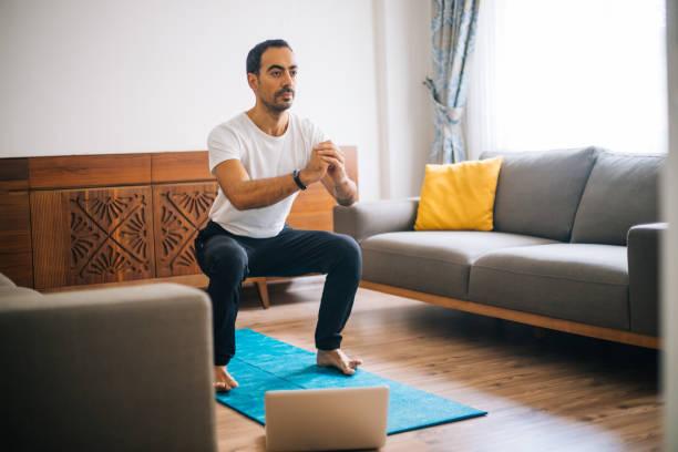 muscular athletic fit man en camiseta y shorts está haciendo ejercicios en cuclillas en casa - agacharse fotografías e imágenes de stock