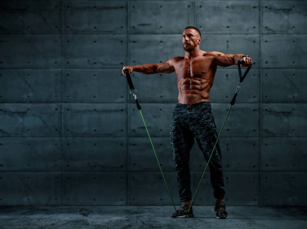 Muscular Athletic Men Exercise With Resistance Band. Copy Space stock photo