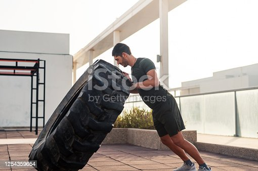 Muscular body builder flipping a tractor tire. Man exercising outdoors for a healthy fitness lifestyle