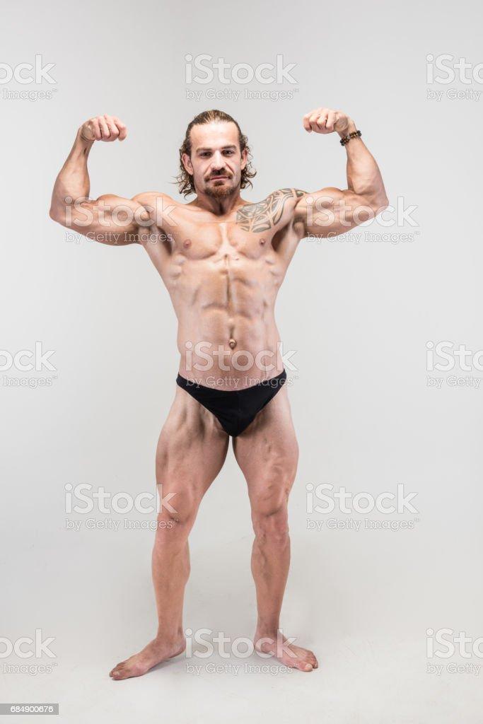 Muscular bodybuilder full body shoot showing biceps Lizenzfreies stock-foto
