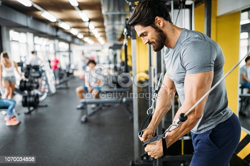 istock Muscular bodybuilder guy doing exercises in gym 1070034858