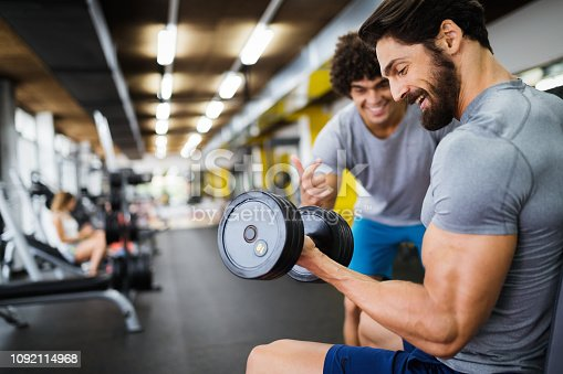 istock Muscular bodybuilder guy doing exercises in gym 1092114968