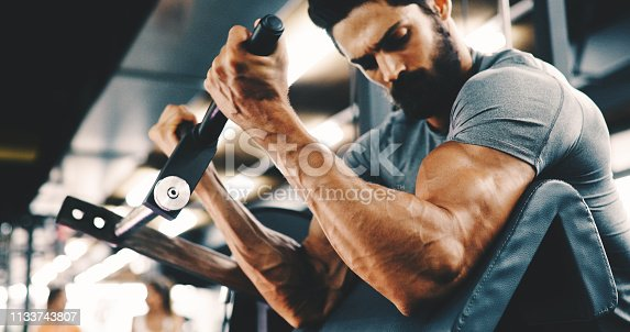 istock Muscular bodybuilder guy doing exercises in gym 1133743807