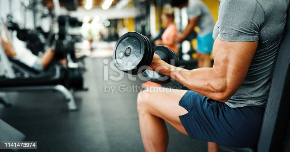 istock Muscular bodybuilder guy doing exercises in gym 1141473974
