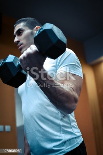 istock Muscular bodybuilder guy doing exercises 1075605952