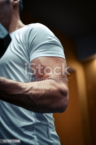istock Muscular bodybuilder guy doing exercises 1075612396
